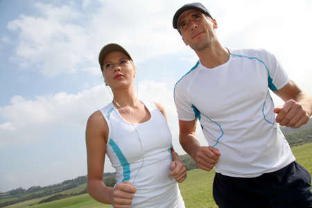 Couple running outside on a sunny day photo