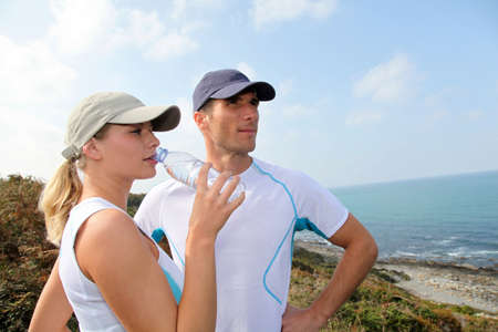 Couple drinking water after exercising photo