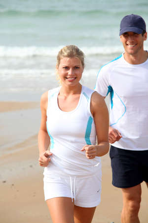 Athletic couple running by the sea in summer photo