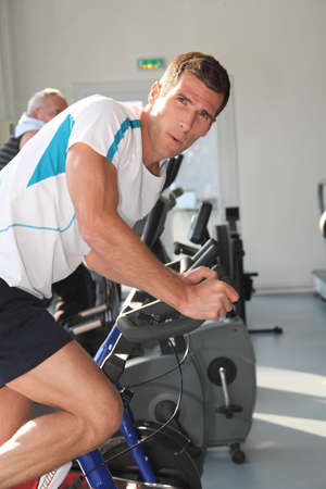 static bike: Closeup of man working out in gym Stock Photo