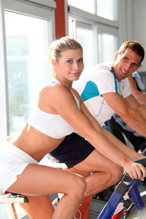 working out: Man and woman doing indoor biking