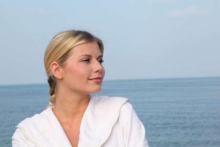 thalasso: Souriante belle femme debout par la mer en peignoir