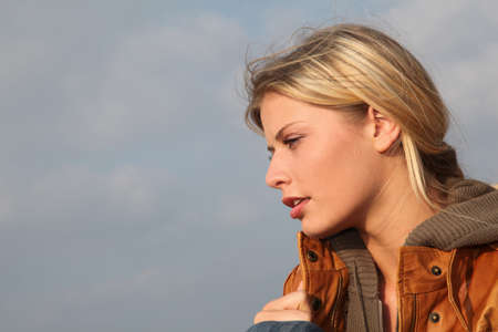 Closeup of woman sitting by the beach in autumn photo