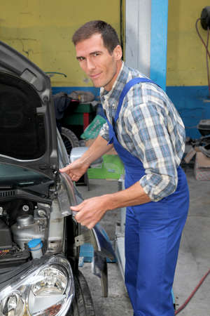 Repairer working on vehicle in garage photo