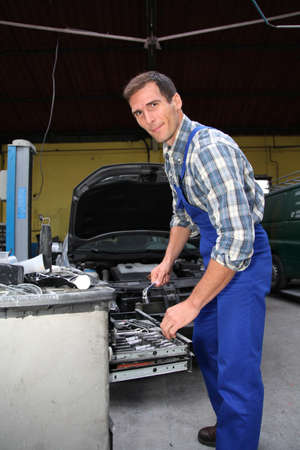 repairer: Repairer working on vehicle in garage