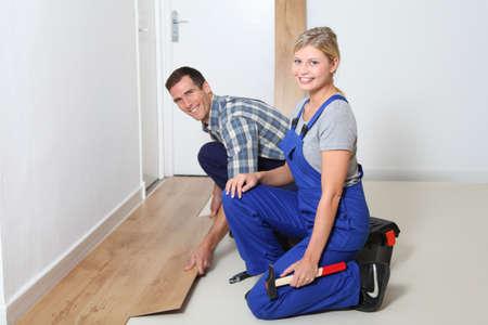 Gros plan des artisan installer des revêtements de sol en salle