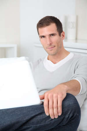 35 years old man: Closeup of adult man sitting on sofa with laptop computer Stock Photo