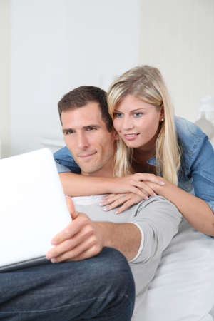 Closeup of couple sitting in sofa surfing on internet Stock Photo - 8088258