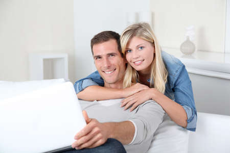 Closeup of couple sitting in sofa surfing on internet photo