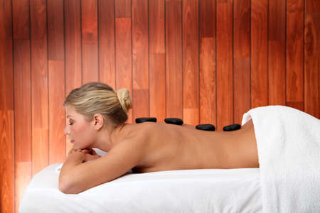 massage stones: Blond woman laying on massage bed with hot stones