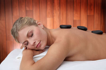 Blond woman laying on massage bed with hot stones photo