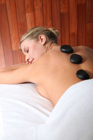 thalasso: Blond woman laying on massage bed with hot stones