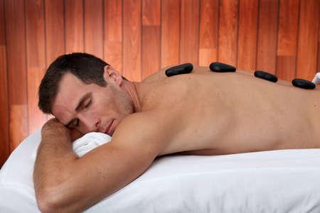 thalasso: Homme relaxant sur lit de massage aux pierres chaudes