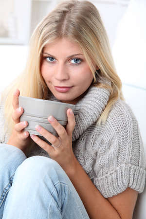cocooning: Beautiful woman drinking hot drink in winter