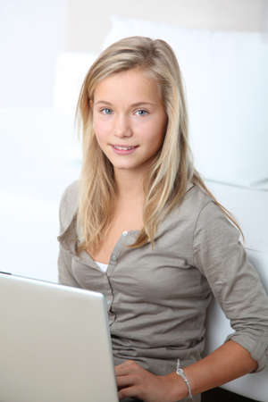 Blond girl sitting in sofa surfing on internet