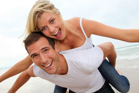 pareja de esposos: Feliz pareja disfrutando de vacaciones en una playa de arena  Foto de archivo