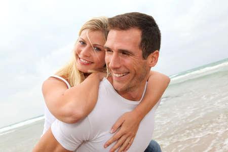 pareja casada: Feliz pareja disfrutando de vacaciones en una playa de arena  Foto de archivo