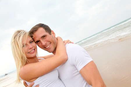 Couple having fun on a sandy beach photo
