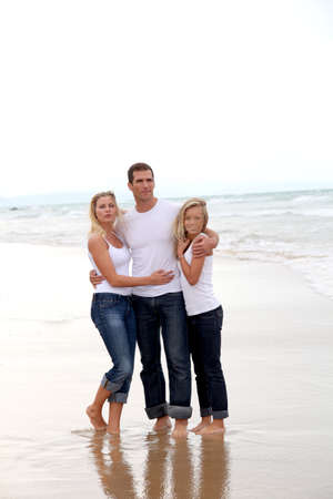 Family walking hand to hand on a sandy beach photo