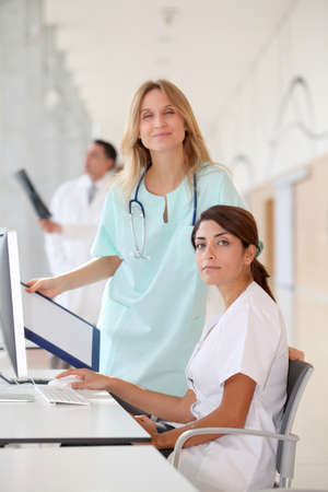 apprentice: Nurse with intern working in front of computer Stock Photo