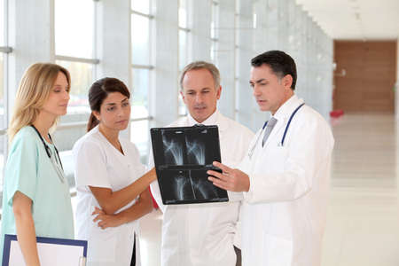 Group of doctors and nurses looking at xray photo
