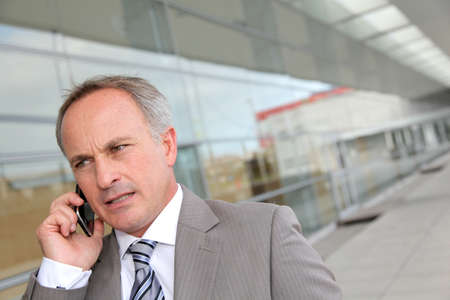 Businessman with mobile phone in front of modern building photo