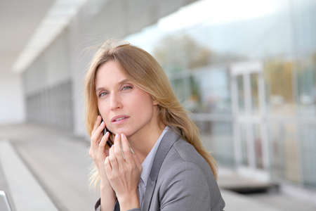 Businesswoman on the phone in front of modern building photo