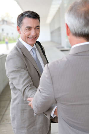 Businessmen shaking hands outside building photo