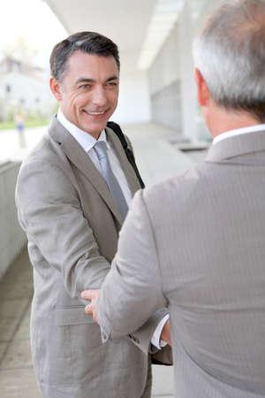 Businessmen shaking hands outside building photo