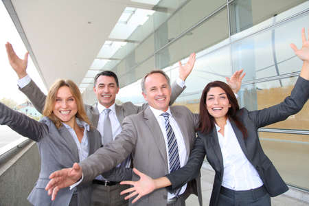 men 45 years: Group of happy business people with arms up