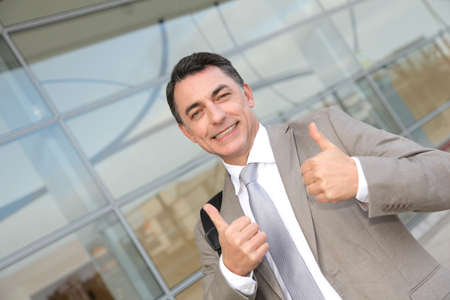 Businessman standing outside modern building photo