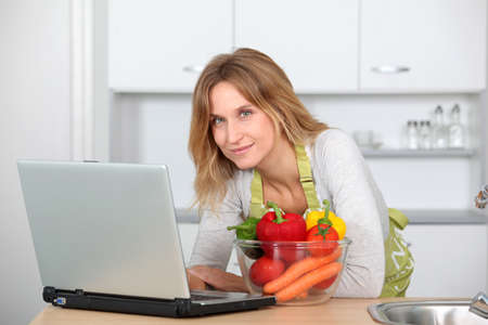 Woman in kitchen looking for cooking receipe photo