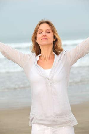 breathe: Woman breathing fresh air by the sea