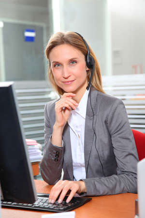 Blond office worker with headphones photo