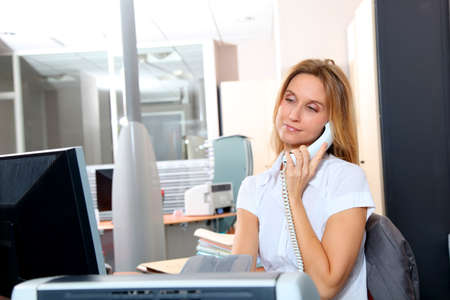 councilor: Blond woman talking on the phone in front of desk computer Stock Photo