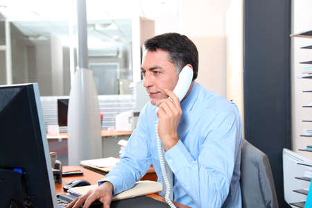 Businessman in the office talking on the phone photo