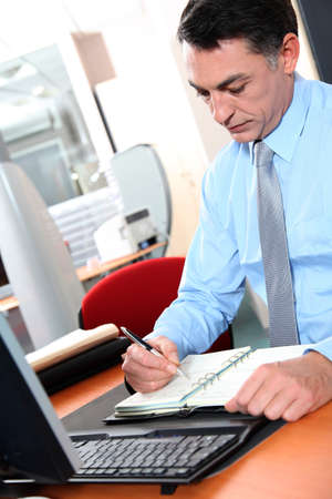 councilor: Businessman at his desk writing down on his agenda