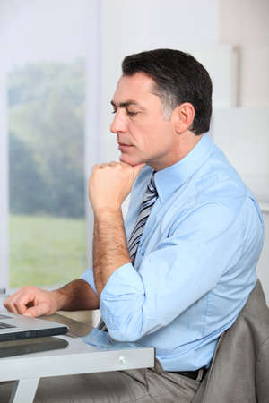 Businessman sitting at his desk with hand on chin photo