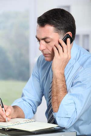 Businessman on the phone writing on agenda photo