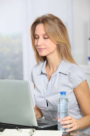 Closeup of beautiful office worker drinking water photo