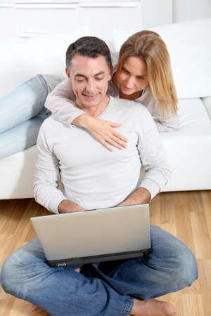 Happy couple surfing on internet at home photo