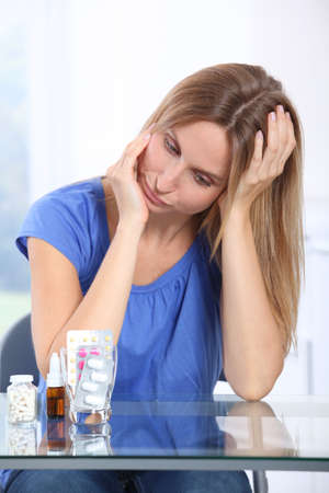 at ease: Woman taking pills to ease migraine