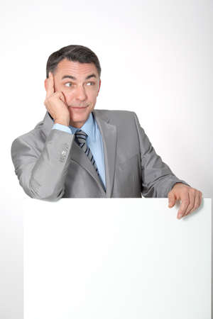 message board: Businessman showing white message board Stock Photo