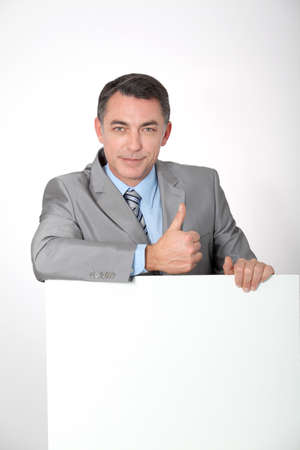 Businessman showing white message board Stock Photo - 8358769