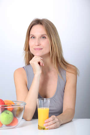 Beautiful blond woman drinking fruit juice photo
