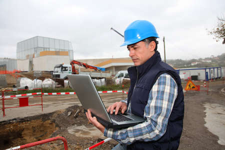 Engineer on construction site with laptop computer photo
