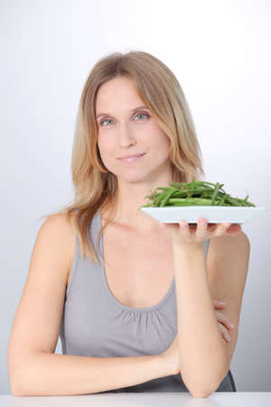 Woman in front of plate of green beans Stock Photo - 8359563