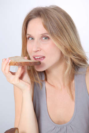 Closeup of beautiful woman eating slice of bread photo