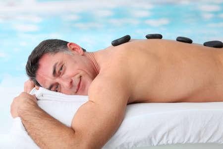 thalasso: Homme pose sur lit de massage aux pierres chaudes Banque d'images