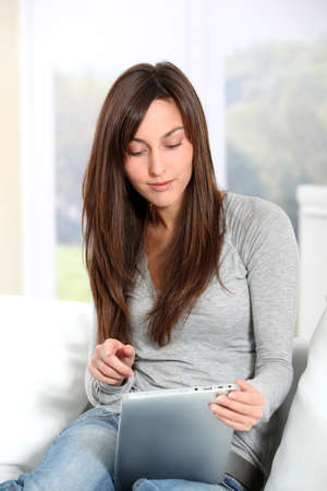 electronic pad: Young woman sitting on sofa with electronic pad Stock Photo
